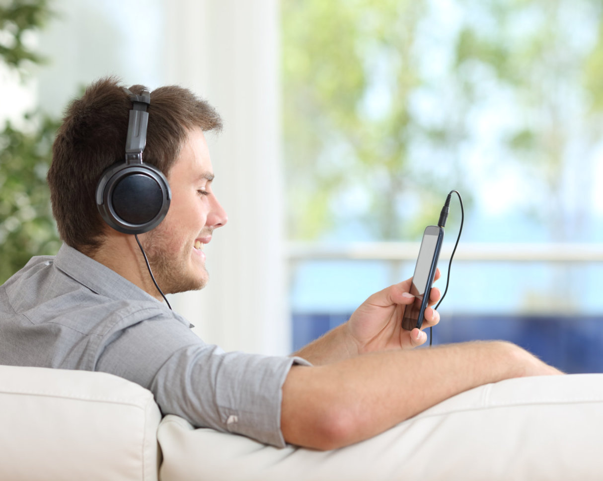 Happy man listens music on phone in the sofa at home.