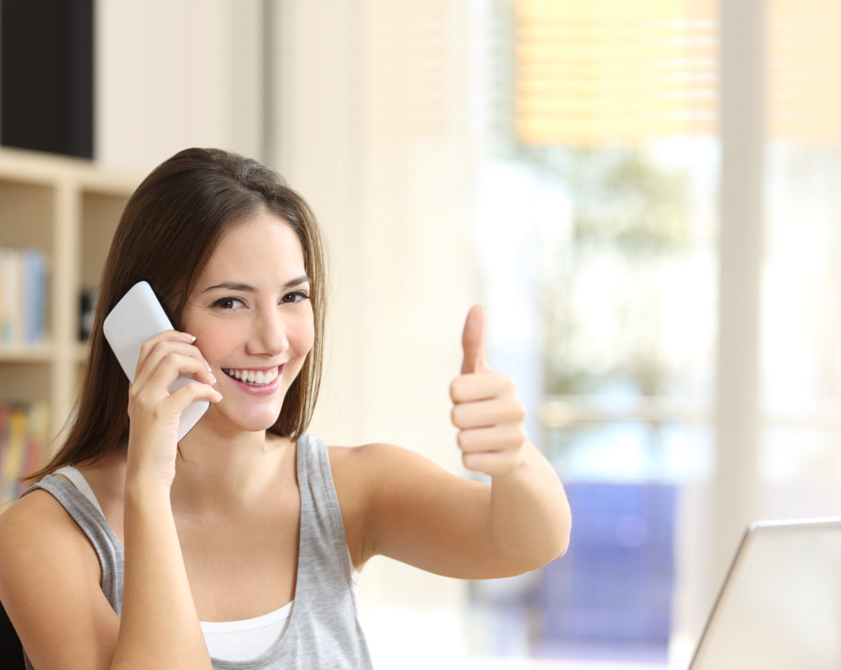 Happy girl calling on phone with thumbs up at home