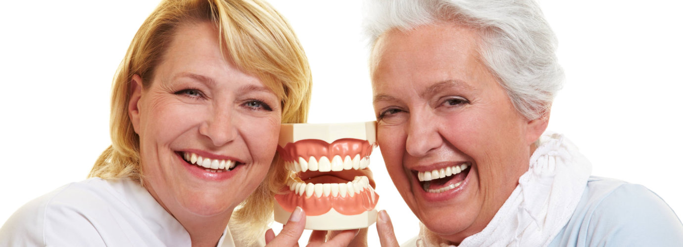 happy dentist and senior woman holding a teeth model